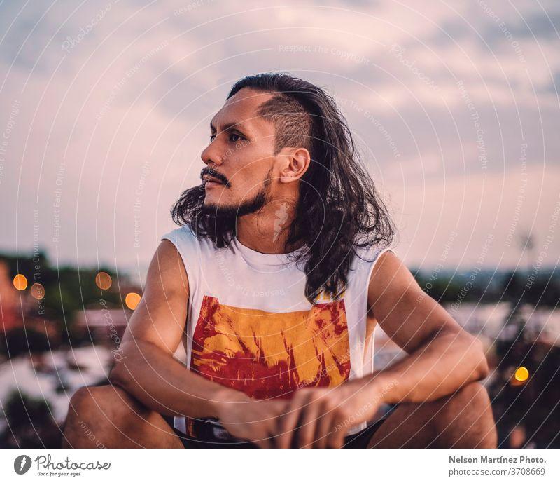 Bildnis eines hispanischen Mannes mit langen Haaren. Wir sehen die Stadt mit einem Bokeh-Hintergrund. vereinzelt Person weiß Erwachsener stolz Vorderseite