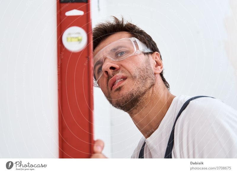 Renovierungskonzept. Männlicher Arbeiter überprüft die Nivellierung der Wand mit der Wasserwaage Werkzeug Niveau Mann Reparatur Heimwerker Konstruktion