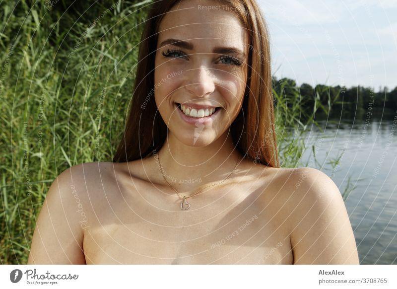 Nahes Portrait einer jungen Frau mit in einem See vor Schilf Licht sportlich feminin Gefühle emotional Blick in die Kamera Porträt Zentralperspektive