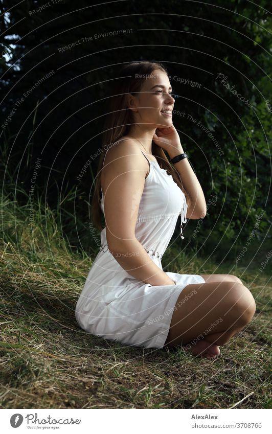 Portrait einer jungen Frau in weißem Sommerkleid im Schneidersitz in der Natur Licht sportlich feminin Gefühle emotional Blick in die Kamera Porträt