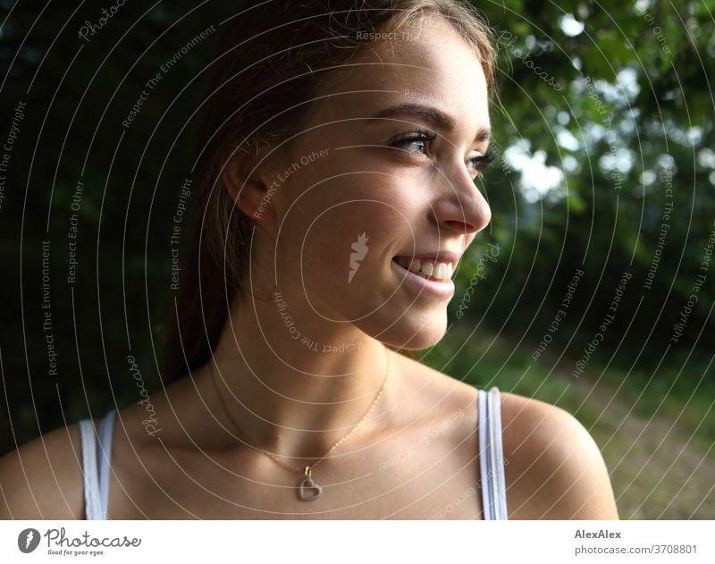 Seitliches, nahes Portrait einer jungen Frau in der Natur Licht sportlich feminin Gefühle emotional Blick in die Kamera Porträt Zentralperspektive