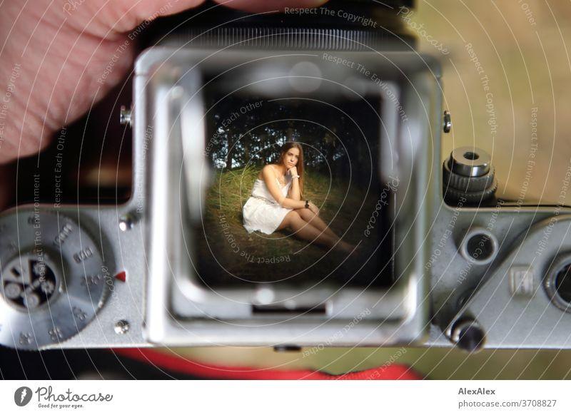 Blick auf den Lichtschacht eine analogen Kamera auf das Bild einer jungen Frau mit weißem Kleid in der Natur sportlich feminin Gefühle emotional Porträt