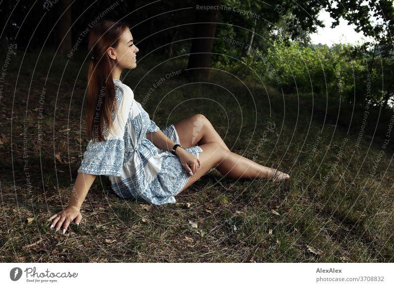 Portrait einer jungen Frau in weiß- blau gemustertem Sommerkleid in der Natur Licht sportlich feminin Gefühle emotional Porträt Zentralperspektive