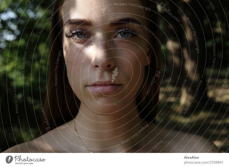 Nahes Portrait einer jungen Frau im Wald Licht sportlich feminin Gefühle emotional Blick in die Kamera Porträt Zentralperspektive Schwache Tiefenschärfe