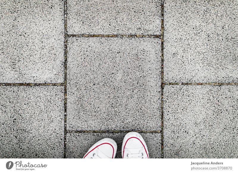 Auf dem Gehweg spazieren Straße gehwegplatten Fußweg Schuhe füße Blick nach unten Asphalt stehen Frau Außenaufnahme grau weiß Tag Mensch Form Muster urban