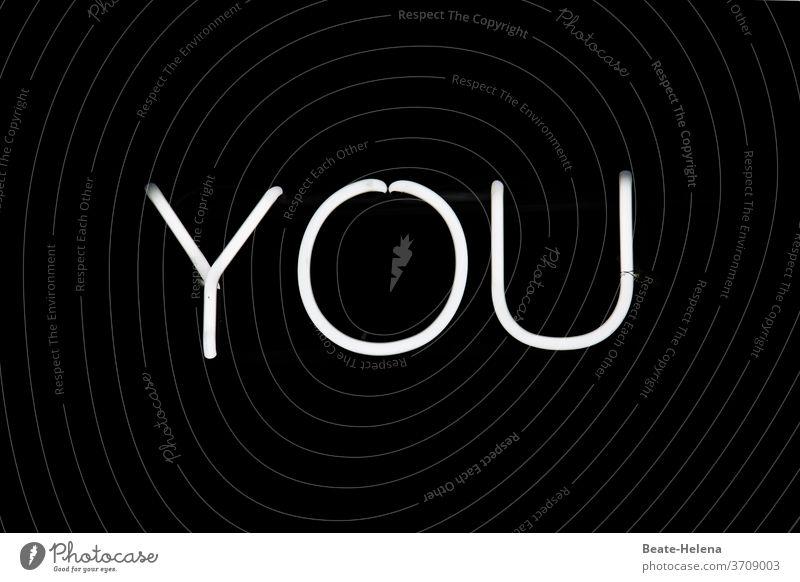 """weiße Leuchtbuchstaben """"YOU"""" auf schwarzem Hintergrund Schriftzeichen leuchten Wand Zeichen LED Graffiti Kommunizieren Leuchtröhre Imperativ Textfreiraum oben"""