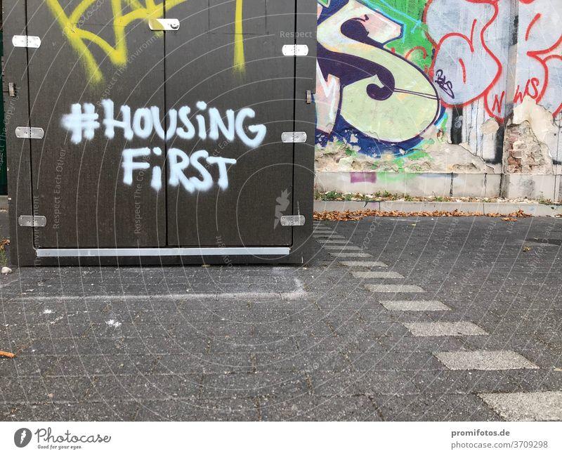 Graffiti mit Hashtag: #HousingFirst / Foto: Alexander Hauk kunst tageslicht außenaufnahmen boden pflastersteine querformat housing housingfirst hashtag
