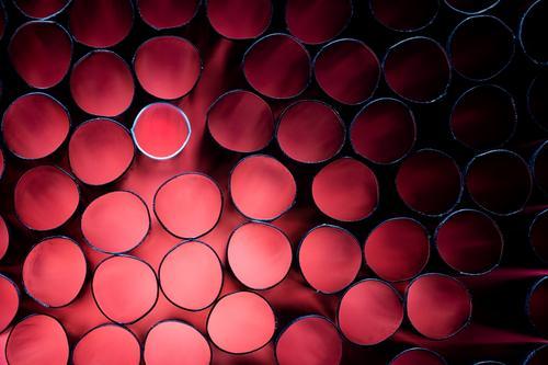 Viele schwarze und ein weisser Trinkhalm mit rotem Licht Röhren weiß Ring Schwache Tiefenschärfe Kunstlicht Studioaufnahme Kunststoff rund Plastikwelt