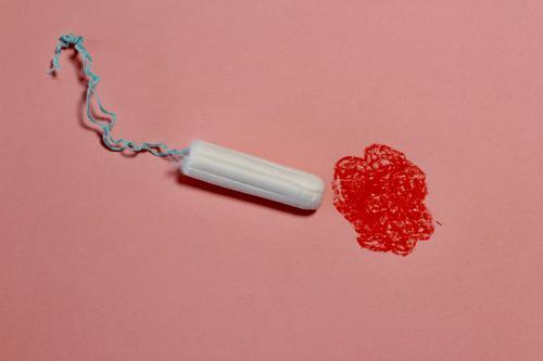 Tampon bewegt sich auf roten, gemalten Fleck zu. Menstruation, Blut, Periode, Regelblutung. menstruation symbolbild periode aufklärung Symbolik feminin Farbfoto
