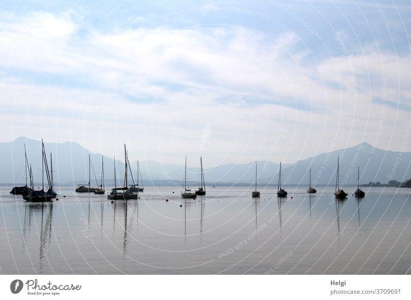 morgens am Chiemsee - viele Segelboote warten am Morgen auf dem Chiemsee auf ihren Einsatz, Spiegelungen im Wasser, Berge im Hintergrund, blauer Himmel mit Wölkchen