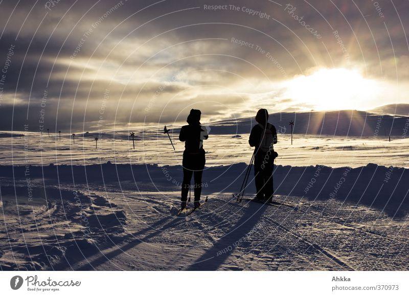 Zwei Menschen in der Sonne vor abendlicher Winterlandschaft Natur Ferien & Urlaub & Reisen Landschaft ruhig Wolken Ferne Berge u. Gebirge Schnee Bewegung