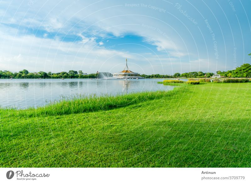 See und grünes Grasfeld am Park. Wasserkreislauf im See in der Nähe des Pavillons. Rasen und Garten im Park im Sommer. Grüner Baum und Grasfeld. Picknick im Urlaub. Menschen entspannen sich und haben Aktivität im Park.
