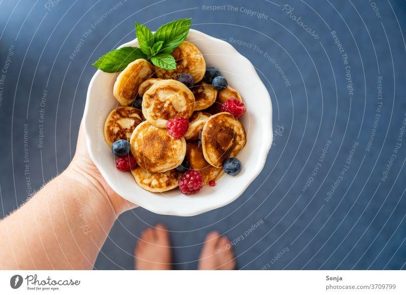 Hand mit frischen kleinen Pfannkuchen in einer weißen Schüssel. Frische Beeren, Draufsicht. Pancakes halten schüssel Barfuß blau fußboden Frühstück gebraten