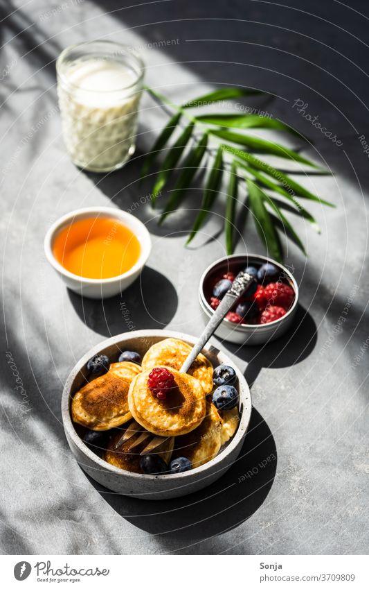 Mini Pancakes mit frischen Beeren und Honig auf einem grauen Tisch. Schlagschatten und Licht, Kontrastreich. Frühstück Dessert süß Pfannkuchen gebraten