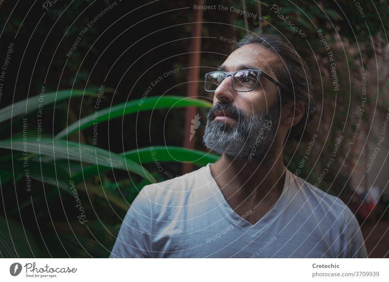 Mann mit Brille seitlich in der Mitte eines Gartens mit einem entspannten Ausdruck sich[Akk] entspannen Senior Intellektueller Zen geistig Meditation weiß Guru