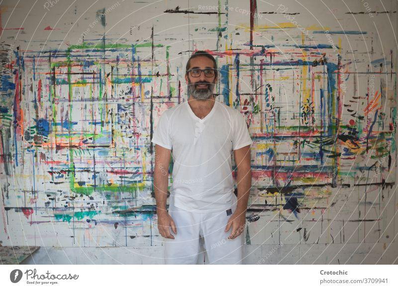 Mann in Weiß gekleidet vor einem Bild stehend Künstler Kreativität Individualität im Innenbereich Pinselblume Fotografie Fähigkeit Stehen Kunst Porträt