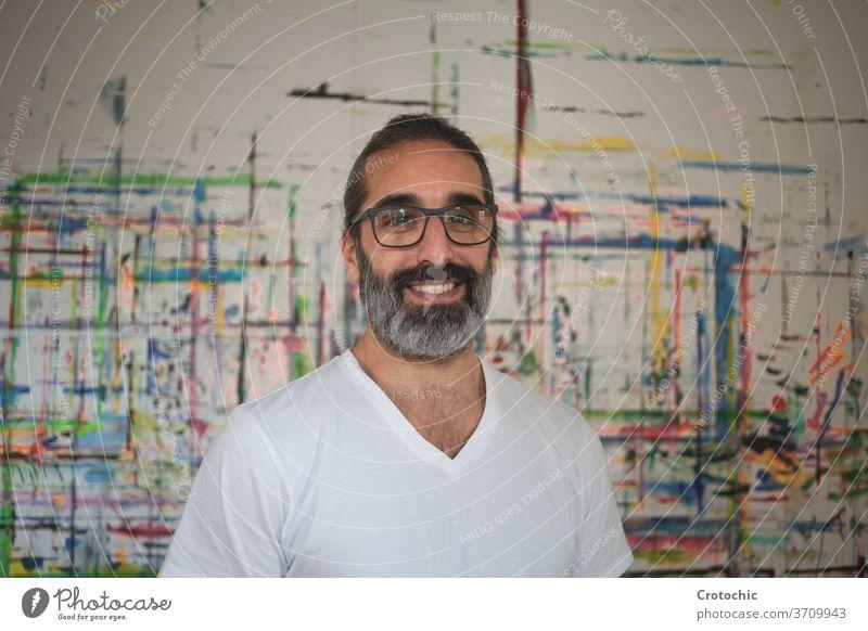 Porträt eines weiß gekleideten Mannes, der vor einem Bild steht Künstler Kreativität Individualität im Innenbereich Pinselblume Fotografie Fähigkeit Stehen