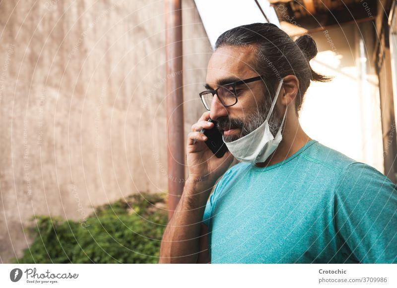 Mann mit Brille, der mit heruntergezogener Maske in sein Mobiltelefon spricht unsicher Fehler ungeschützt Halt Mundschutz Mitteilung Klang Stimme reden COVID