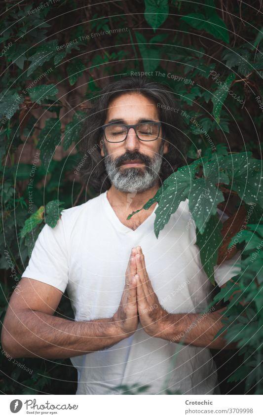 Mann in weiß stehend auf einem Garten mit seinen Händen zusammen in der Meditation hinduistisch chakra meditierend beten Gleichgewicht Pose maskulin bequem rein