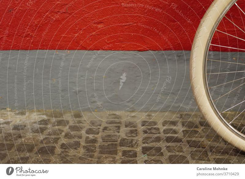 Teil eines Fahrrads an einer bunten Hauswand Rad Pneu Fassade Wand Farbfoto Menschenleer Mauer Außenaufnahme Tag Gebäude Fenster Architektur Bauwerk trist Stadt