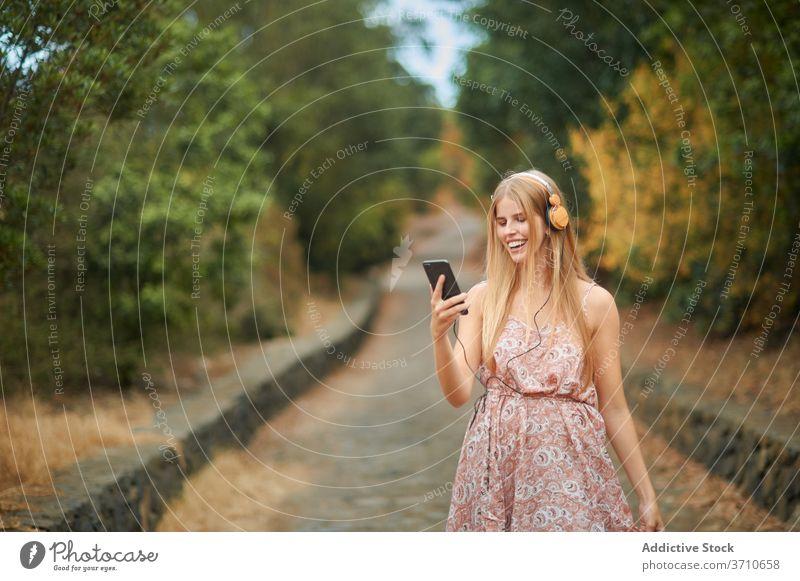 Lächelnde Frau mit Smartphone und Kopfhörer zu Fuß im Park Glück zuhören benutzend Musik Sommer genießen jung Browsen Gasse Weg Gerät Apparatur Lifestyle Stil