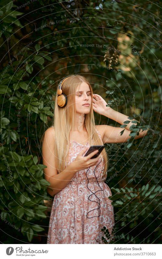 Ruhige junge Frau beim Musikhören im Garten zuhören Smartphone Kopfhörer Gelassenheit sich[Akk] entspannen Windstille genießen blond Technik & Technologie