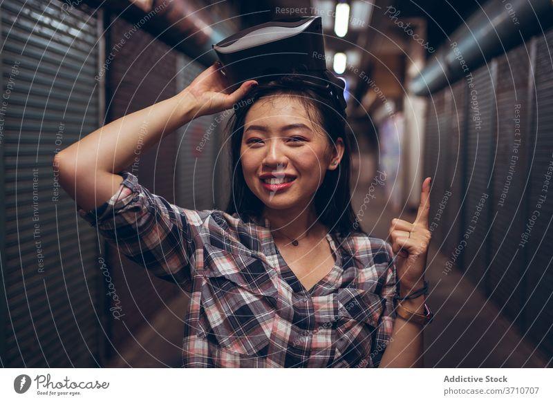 Asiatische Frau mit VR-Brille auf der Straße virtuell Realität Schutzbrille Virtuelle Realität nach oben zeigen gestikulieren Erfahrung asiatisch ethnisch Index