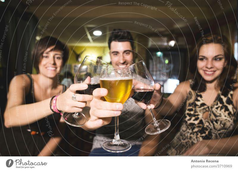 Drei Freunde im Restaurant mit Alkoholbechern, die auf die Aussicht anstoßen Bar Zuprosten Getränke Erwachsene Kaukasier Bier Wein trinken Essen Frauen