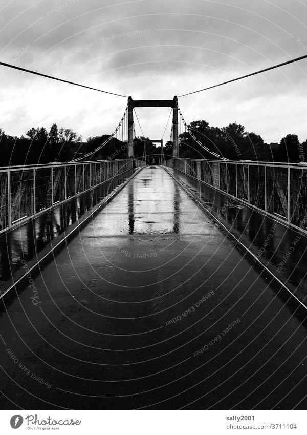 Brücke im Regen... schmal Fußgängerbrücke Geländer Hängebrücke Asphalt schlechtes Wetter nass Schwarzweißfoto Spiegelung Reflexion & Spiegelung Wege & Pfade