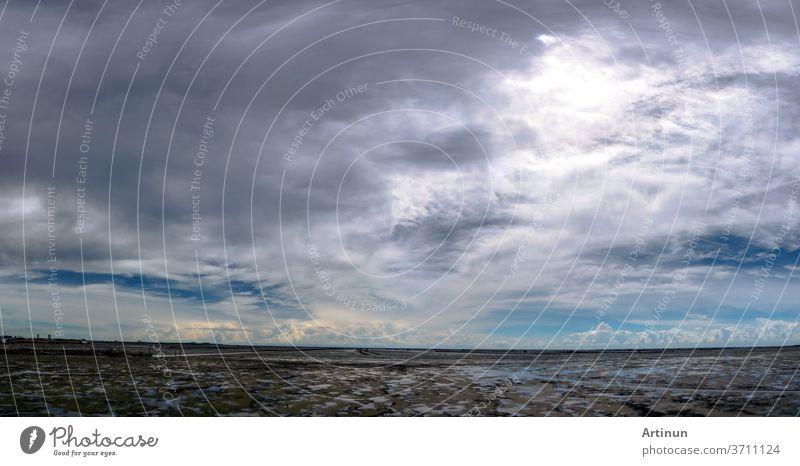 Landschaft mit Schlammstrand, Meer und Himmel. Panorama-Ansicht des Strandes bei Flut und Skyline. Wunderschöne Wolkenlandschaft. Blauer Himmel und weiße Wolken an einem sonnigen Tag. Tropisches Meer. Konzept für Sommerreisen. Der Klimawandel.