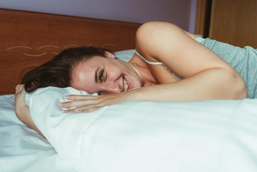 Nahaufnahme-Porträt einer lächelnden attraktiven Frau, die auf dem Bett liegt und in die Kamera schaut. Menschen Erwachsener Mädchen Raum Schlafzimmer Familie