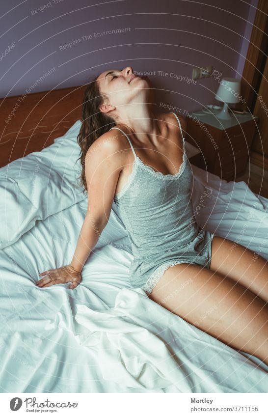 Von oben junge Frau, die mit geschlossenen Augen auf einer weißen Bettdecke sitzt und am Morgen lacht. schön zu Hause im Schlafzimmer bleiben Lifestyle Pyjama