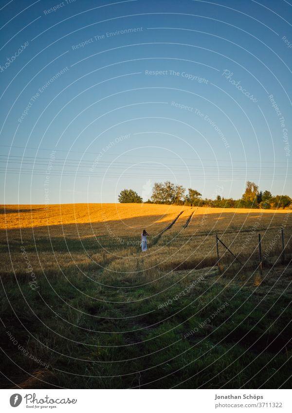 junge Frau läuft auf einem Feldweg in der Abendsonne Ernte Feldrand Getreide Getreidefeld Gluten Himmel Junge Frau Landwirtschaft Rückansicht Sommer Strom