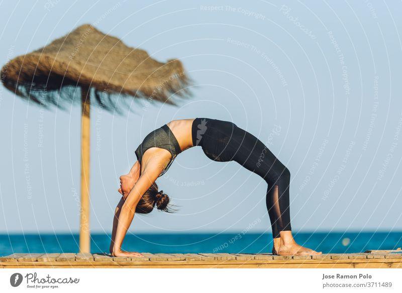junge Frau bei einer Yoga-Brückenübung am Strand vor dem Meer neben einem Sonnenschirm auf Menschen Übung Meditation Person Sport Fitness Erholung Wellness