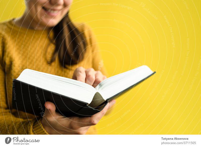 Studentin mit Büchern auf Gelb Frau Schüler Bildung Buch Universität Hochschule gelb lesen Pullover gestrickt Person Erwachsener studierend Menschen Porträt