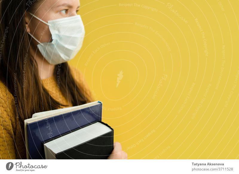 Studentin mit Büchern über Gelb in der Gesichtsmaske Frau Schüler Bildung Buch Universität Hochschule gelb lesen Pullover gestrickt Person Erwachsener