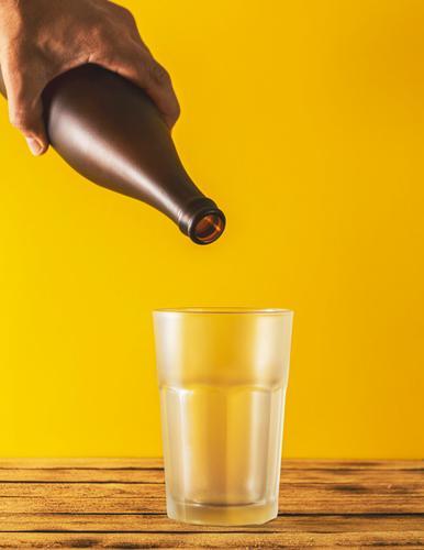 Leeres Bierglas, Flaschenbier auf Holzuntergrund und gelber, selektiver Fokus. Bierflaschen Club Oktoberfest Glas bayerisch Stadtfest München Schuss Bayern