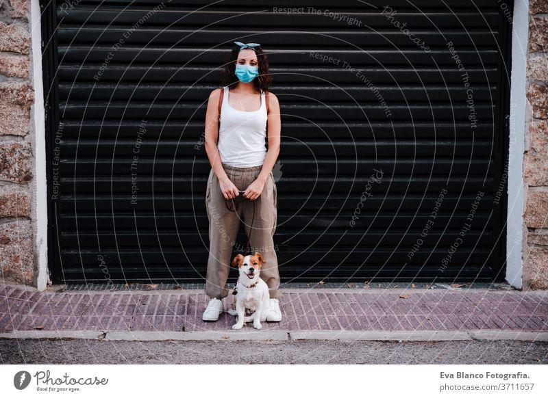 junge Frau im Freien mit Schutzmaske, daneben süßer Jack-Russell-Hund. Neues normales Konzept Straße neue Normale jack russell Haustier laufen urban Großstadt
