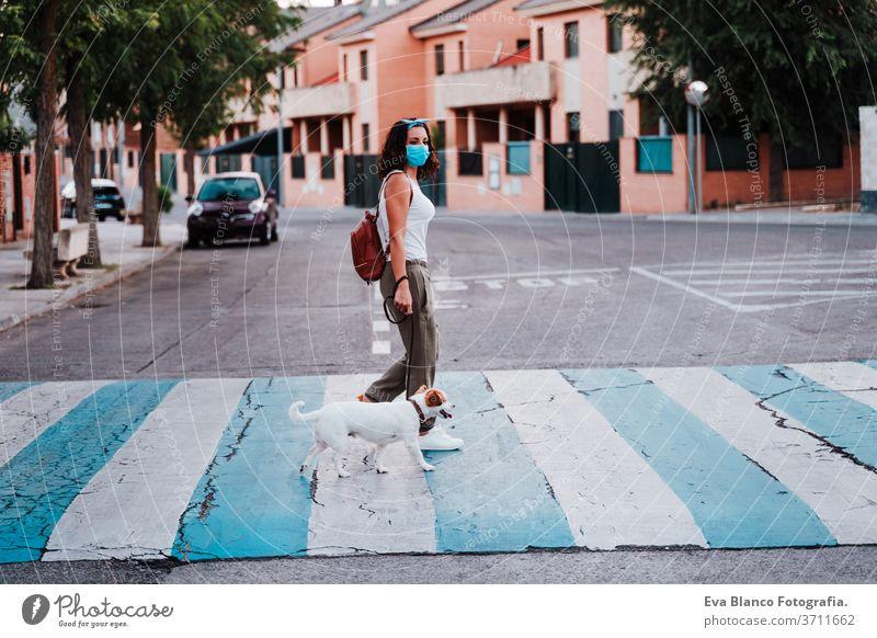 junge Frau am Fußgängerüberweg mit Schutzmaske, daneben süßer Jack-Russell-Hund. Neues normales Konzept Straße neue Normale jack russell Haustier laufen urban