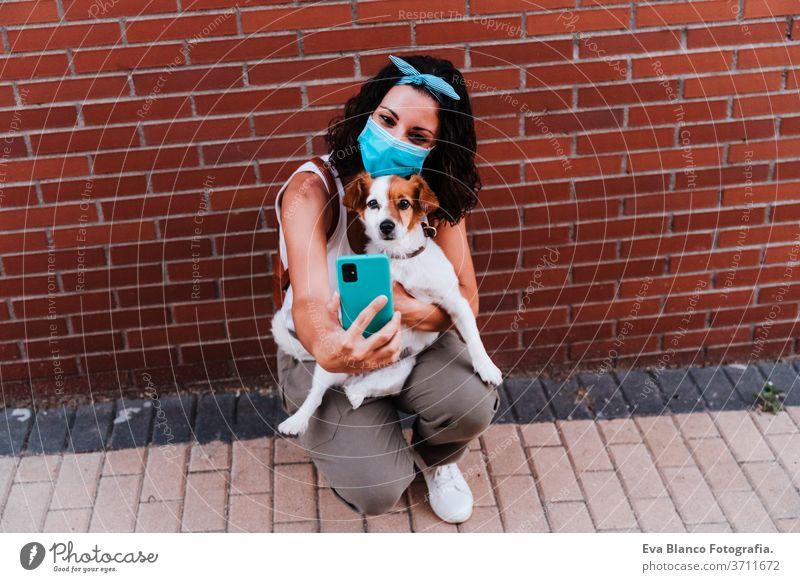 junge Frau, die mit einer Schutzmaske im Freien spazieren geht und mit ihrem Handy ein Foto des süßen Hundes Jack Russell macht. Neues normales Konzept Straße