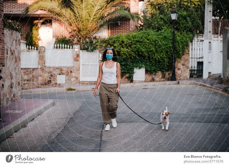 junge Frau, die mit Schutzmaske im Freien spazieren geht, daneben süßer Jack-Russell-Hund. Neues normales Konzept Straße neue Normale jack russell Haustier