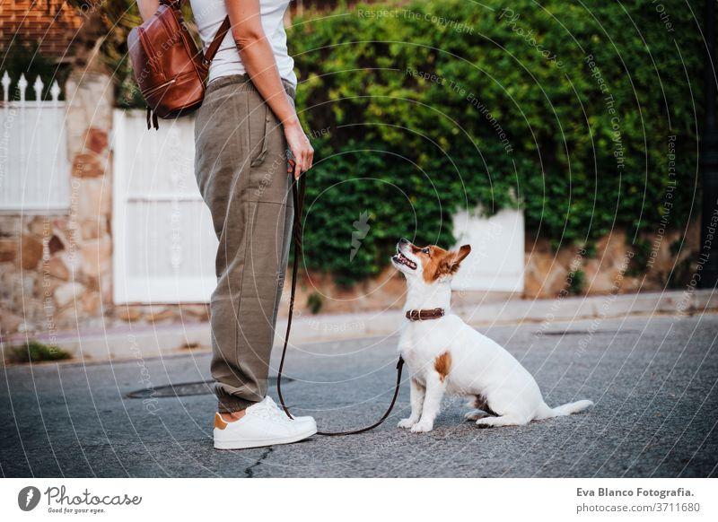 Nahaufnahme einer jungen Frau im Freien mit Schutzmaske, daneben süßer Jack-Russell-Hund. Neues normales Konzept Straße neue Normale jack russell Haustier