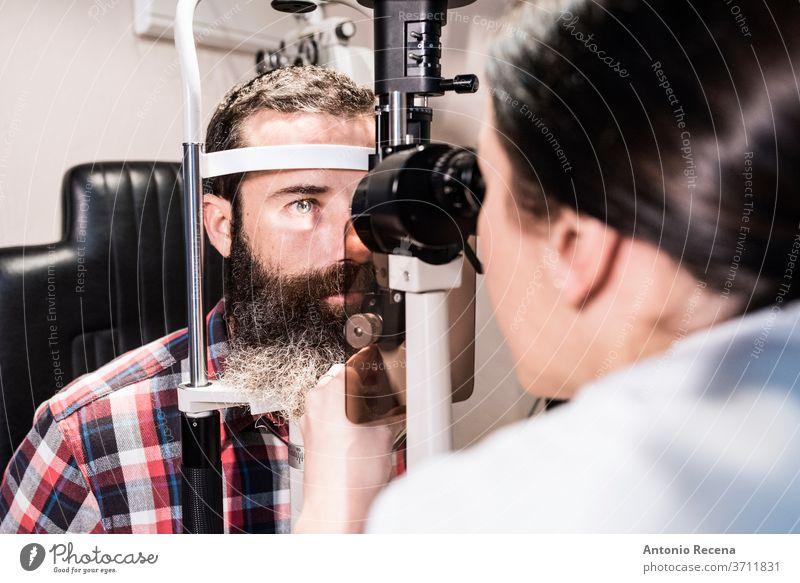 Frau untersucht das Sehvermögen eines bärtigen Mannes im optischen Zentrum mit einer Spaltlampe Optik Ophthalmologie Prüfung arbeiten Arbeiter Apotheke Person