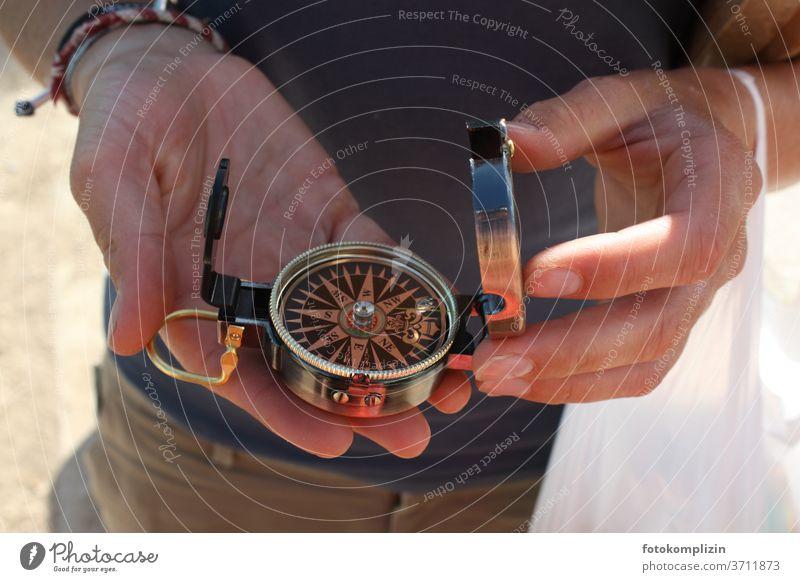 zwei Hände halten einen kleinen Kompass Richtung richtungsweisend Richtungswechsel Orientierung Navigation Himmelsrichtung Wegweiser Hinweis Empfehlung zeigen