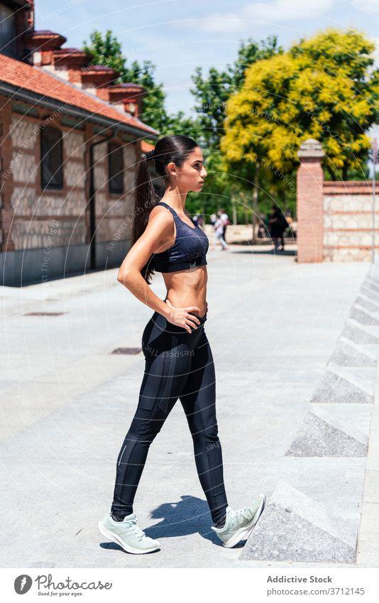 Sportliche Frau streckt die Beine auf der Straße Sportlerin Dehnung Ausfallschritt Übung Training Athlet Fitness schlank jung Sportbekleidung Wellness passen