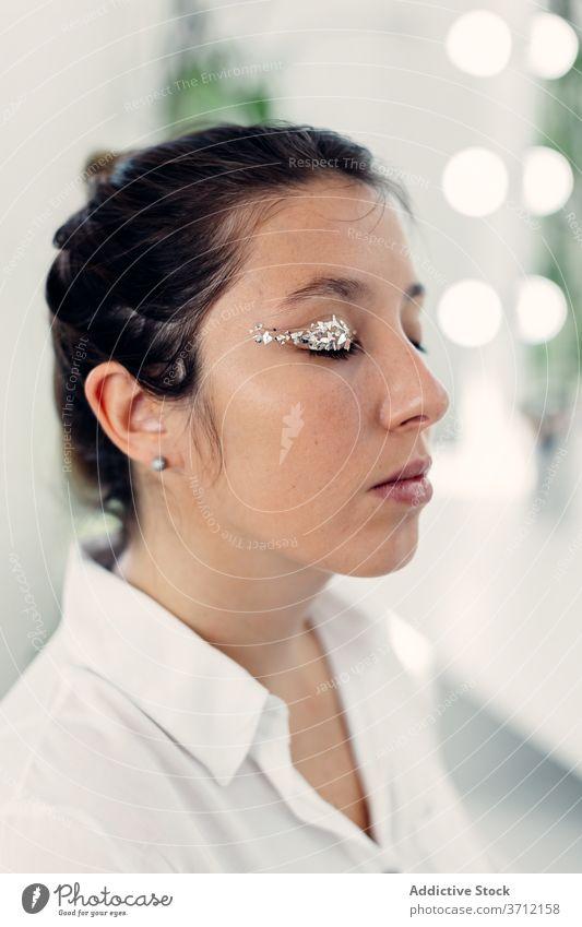 Frau mit professionellem Make-up im Salon Lidschatten Model Glitter zeigen Gesicht hell Schönheit Atelier charmant Stil Glamour Augen geschlossen Kosmetik