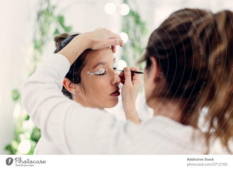Visagistin beim Schminken im Salon Make-up professionell Künstler Kajal Glitter bewerben visagiste Frauen Zusammensein Model Atelier Schönheit Kosmetik elegant