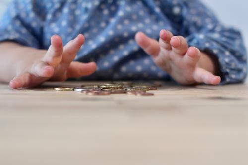 Taschengeld. Ein Kind spielt  an einem Holztisch mit Geldmünzen,Cents . Kinderhände euro geldmünzen kind neugierde erkunden kinderhände muster punkte