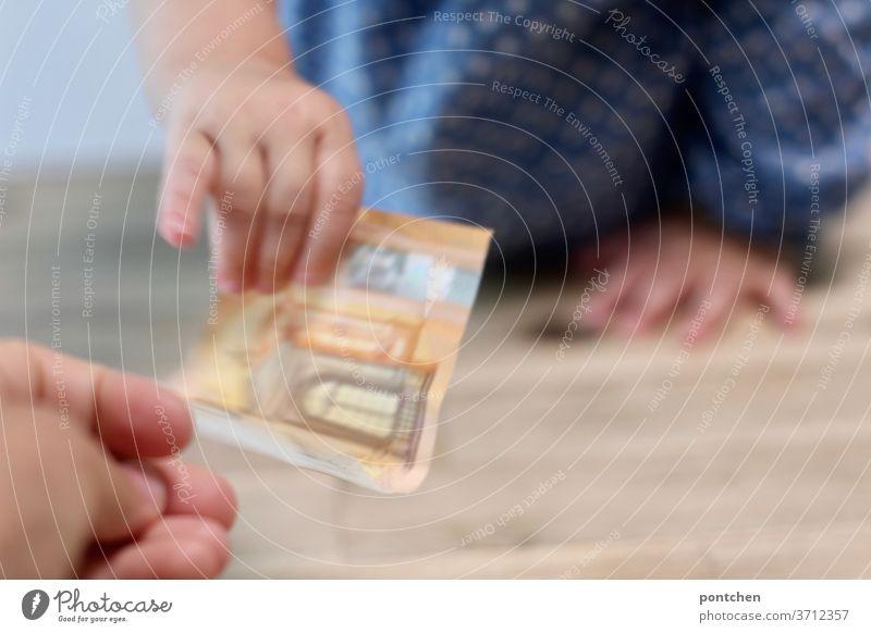 Kinder kosten Geld. Ein 50 Euro Schein wechselt von der Hand einer Erwachsenen zur Hand eines Kindes. Geld hergeben, Geld  ausgeben. Kosten. Kindergeld. Familiengeld.