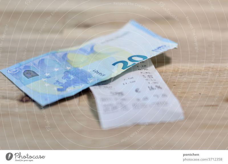 Ein 20 Euro Schein liegt auf einer Rechnung. Bezahlen, Trinkgeld Geldschein kassenbon trinkgeld bezahlen Kapitalwirtschaft Bargeld Business Wirtschaft